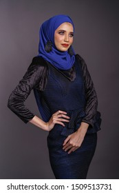 Beautiful female model wearing dark color peplum dress with hijab, a modern lifestyle outfit for Muslim woman isolated over grey background. Stylish female hijab fashion lifestyle portraiture concept.