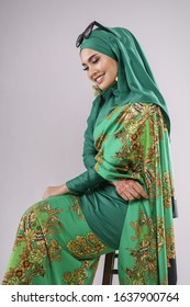 "Beautiful female model wearing green batik design ""baju kurung"" with  hijab, sitting in various poses isolated over white background. Eidul fitri fashion and beauty concept."