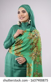 "Beautiful female model wearing green batik design ""baju kurung"" with hijab, a modern lifestyle outfit  for Muslim woman isolated over white background. Eidul fitri fashion and beauty concept."