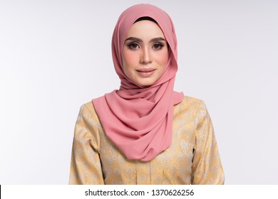 Beautiful female model wearing kebaya made from songket with hijab, an Asian traditional dress for Muslim woman isolated over white background. Eidul fitri fashion and beauty.
