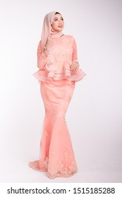 Beautiful female model wearing light peach peplum dress with hijab, a modern lifestyle outfit for wedding ceremony isolated over white background. Malay wedding dress concept.