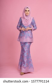 "Beautiful female model wearing light purple batik design ""baju kurung"" with hijab, a modern lifestyle outfit  for Muslim woman isolated over pink background. Eidul fitri fashion and beauty concept."