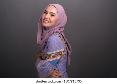 Beautiful female model wearing modern kebaya, an Asian traditional dress for Muslim woman isolated over grey background. Stylish Muslim female hijab fashion lifestyle portraiture concept.