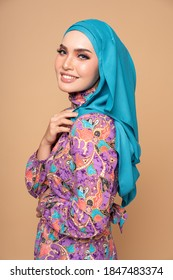 Beautiful female model wearing modern batik kebaya with hijab, an Asian traditional dress for Muslim woman isolated over beige background. Stylish Muslim female fashion lifestyle  concept.