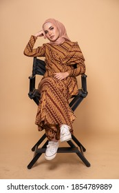 Beautiful female model wearing modern batik kebaya with hijab, sitting on a director chair isolated over beige background. Stylish Muslim female fashion lifestyle portraiture concept.