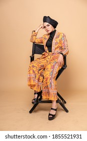 Beautiful female model wearing modern batik kebaya with turban style hijab, sitting on a director chair isolated over beige background. Stylish Muslim female fashion lifestyle portraiture concept.