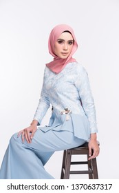 Beautiful female model wearing peplum dress with hijab, a modern lifestyle outfit  for Muslim woman isolated over white background. Eidul fitri fashion and beauty concept.