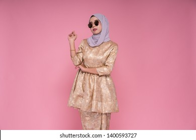 Beautiful female model wearing peplum dress with hijab, a modern lifestyle outfit  for Muslim woman isolated over pink background. Eidul fitri fashion and beauty concept.