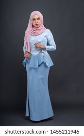 Beautiful female model wearing peplum dress with hijab, a modern lifestyle outfit  for Muslim woman isolated over grey background. Studio hijab fashion and beauty concept
