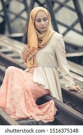Beautiful female model wearing peplum dress with hijab, posing on abandoned railroads bridge. Stylish Muslim hijab fashion lifestyle portraiture concept.