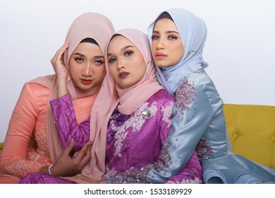 Beautiful female models wearing peplum dress with hijab, a modern lifestyle outfit for Malaysian woman sitting on a couch isolated over white background. Wedding, lifestyle and beauty concept.