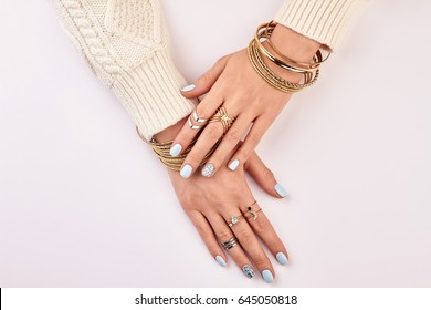 Beautiful female nails with manicure. Fashion manicure with rings and bracelets.