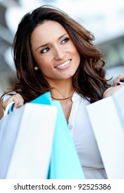 Beautiful female out shopping holding paper bags outdoors
