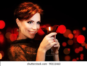 Beautiful female partying, celebrating holiday, portrait of a woman holding martini glass, girl over black background with red blur bokeh lights, luxury nightlife