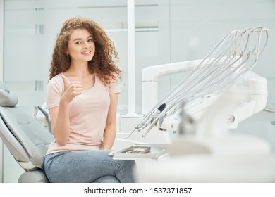 Beautiful female patient in pink shirt and jeans visiting dental office. Pretty woman looking at camera, smiling and showing sign ok in clinic. Concept of medicine and treatment.