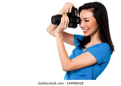 Beautiful female photographer taking a snap. Isolated over white background.