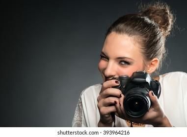 Beautiful female photographer using her camera in studio.