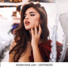 Beautiful female posing for the fashion magazine cover in a restaurant near silver designer vase. Demonstrate perfect red cocktail dress with decollete and open shoulder. Hand on he face, looking away