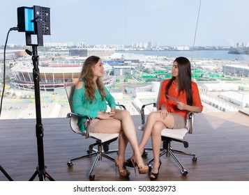Beautiful female presenter interviewing a famous woman at tv studio
