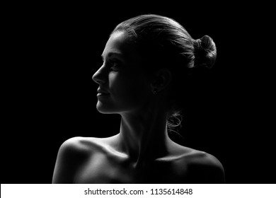 beautiful female profile with bare shoulders on black background, monochrome