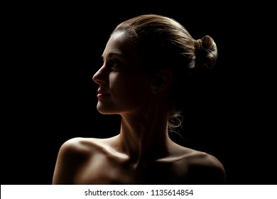 beautiful female profile with bare shoulders on black background