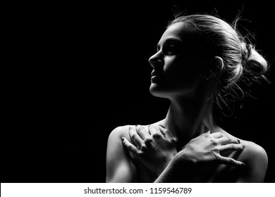 beautiful female profile with bare shoulders on black background with copy space, monochrome