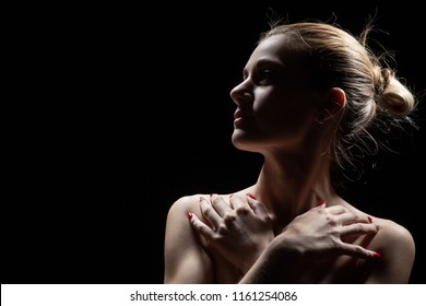 beautiful female profile with bare shoulders on black background with copy space
