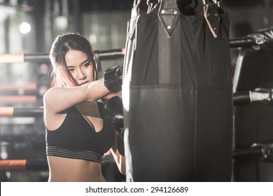 Beautiful Female Punching A Boxing bag With Boxing Gloves at the gym. concept about sport, fitness, martial arts and people