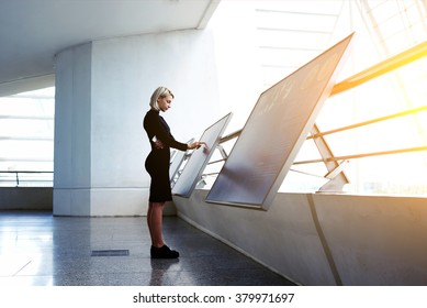 Beautiful female reading advertising about a project on interactive computer display while standing in office interior, businesswoman searching information on high tech modern device