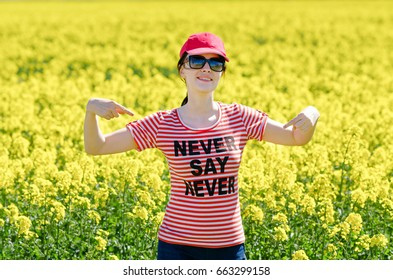 Beautiful female in red cap and t-shirt with Never say never text. Woman is smiling and showing you a phrase. Girl are happy and show you enjoyment