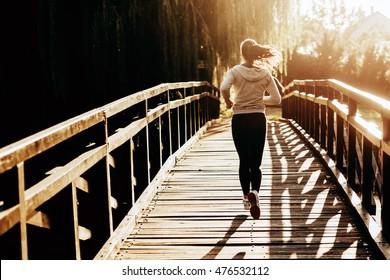 Beautiful female runner jogging in nature