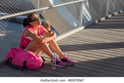 Beautiful female runner resting and eating an apple on a bridge
