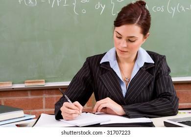 beautiful female school teacher preparing for the class