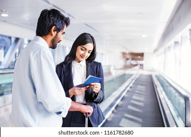 Beautiful female security officer in airport checking documents of a traveler