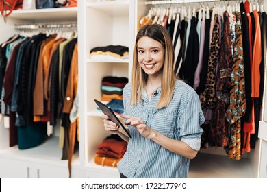 Beautiful female seller working in exclusive boutique or store.