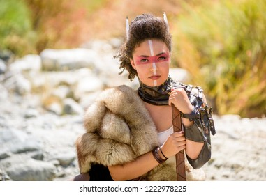 A beautiful female shield maiden character with fur and an ax in the foothills of a mountain. Fashion editorial influences