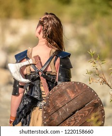 A beautiful female shield maiden viking character with fur and an ax walking away from the camera. Fashion editorial influences