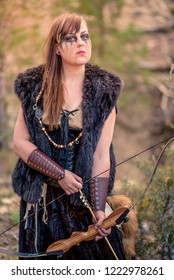 A beautiful female shield maiden viking character with real fur and a reflex bow in the mountains. Fashion editorial influences