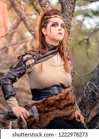 A beautiful female shield maiden viking character with real fur and a small axe in the mountains. Fashion editorial influences