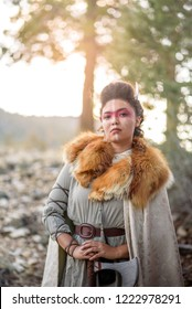 A beautiful female shield maiden viking character with real fur and an axe in the mountains. Fashion editorial influences