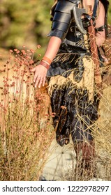 A beautiful female shield maiden viking character brushes her hands over some wild foliage. Fashion editorial influences