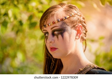 A beautiful female shield maiden viking character with fur and an ax in the foothills of a mountain. Fashion editorial influences
