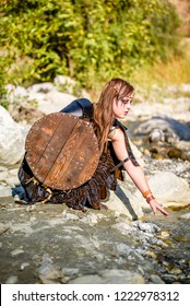 A beautiful female shield maiden viking character with fur and an ax in the foothills of a mountain. Model reaching into a creek. Fashion editorial influences