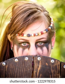 A beautiful female shield maiden viking character partially covering her face with her shield. Fashion editorial influences