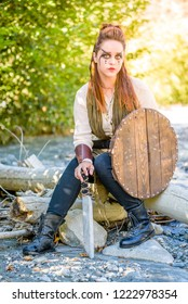 A beautiful female shield maiden viking character with fur and saex knife in the foothills of a mountain. Fashion editorial influences