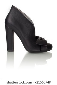 Beautiful female shiny leather black luxury shoe decorated with a bow on high heel on a white background, side view