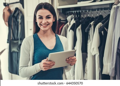 Beautiful female shop assistant is using a digital tablet, looking at camera and smiling while standing in boutique