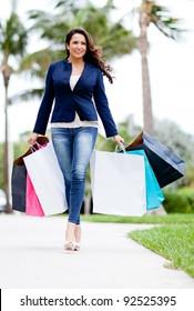 Beautiful female shopper with bags walking outdoors