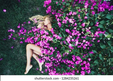 Beautiful female sleeping outdoor in nature under bougainvillea flowers