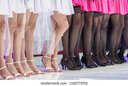 Beautiful female slim feet of group of girls, half wear black silk stockings and half bare legs.